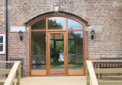 Timber arched glazed door in period barn conversion